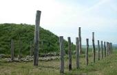 12: Stolpemarkering af stenalder- huset som lå på stedet før højen.