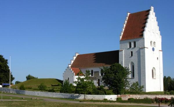 1: Elmelunde Kirke set fra nordvest med den store gravhøj på kirkegården lige øst for kirken.