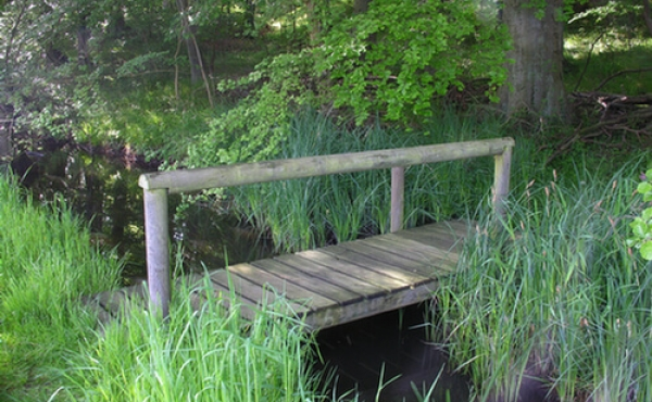 11: En lille træbro fører over den regulerede Hulebæk til Storke- skoven.