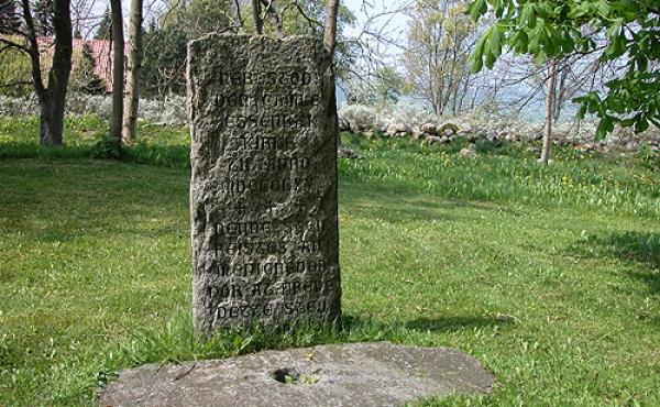 I nordvest-hjørnet står en mindesten over kirkestedet.