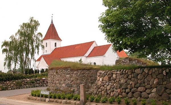 Malling Kirke set fra sydøst. Middelaldertårnet indgår i stenmuren omkring kirkegården.
