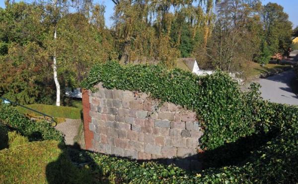De restaurerede murværker efter den tidlige middelalder-rundkirke på kirkegården ved Pedersborg Kirke.