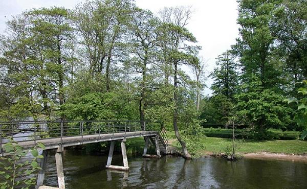 En gangbro fører over Gudenå til Slotsholmen.