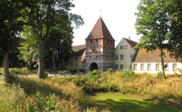 Det gamle befæstede porttårn ved Mølleport set udefra med voldgraven i forgrunden.