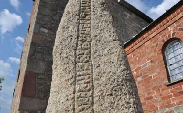 3: Runeindskriften står smukt indhugget lodret på smalsiden af den trekantede granitsten.