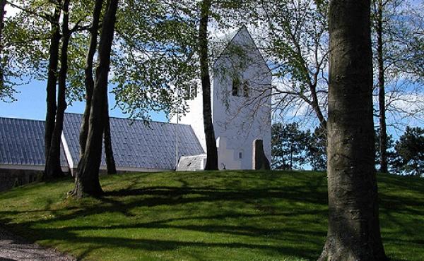 1: Gravhøjen på Rimsø kirkegård set fra nordøst. Omkring 100 danske kirker har tilsvarende hedenske gravhøje ved kirken.