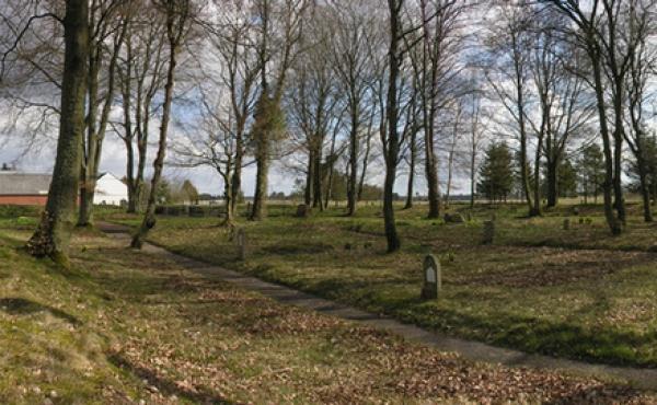 Oversigtsfoto fra nordvesthjørnet af den stemningsfyldte kirkeplads for Grene gamle Kirke. Kirkegården med dens grave omsluttes af et stort stendige og tomten af den gamle kirke er markeret med græs i nordenden af arealet.