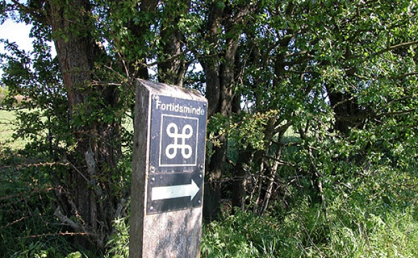 8: Fortidsmindeskiltet ved markskellet viser vej til langdyssen syd for Hovlinen.