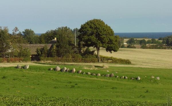 """Langdyssen ved Kraneled ligger flot i marken. Her set fra nordvest med Østersøen i baggrunden. Dyssen er den eneste """"overlevende"""" af tre på stedet."""