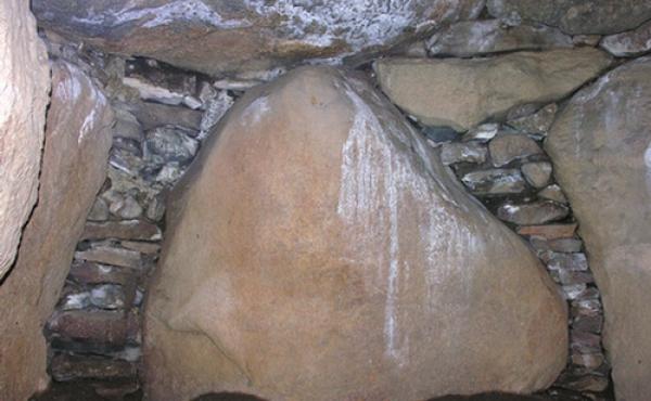 Gavlsten i nordøstenden af kammeret med originale tørmure og indskudte sten, som helt forsegler gravkammeret.